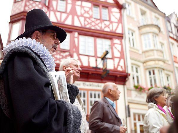 """Wein genießen an der Mosel. Zum Beispiel bei der Erlebnisführung """"Doctor-Wein-Tour"""" in Bernkastel-Kues; im Hintergrund der historische Marktplatz."""