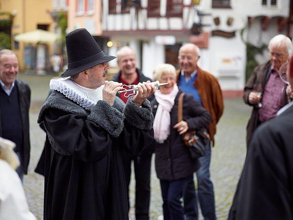 Gästeführer der Doctor-Wein-Tour in Bernkastel-Kues hält Equipment (Spritze) in den Händen.